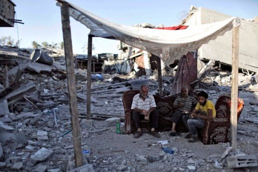 Palestinians sit amid the ruins of destroyed homes in the Shejaia neighbourhood of Gaza City